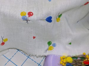 Putting pins through the fabric into the cap