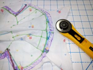 Using rotary cutter to trim off excess fabric